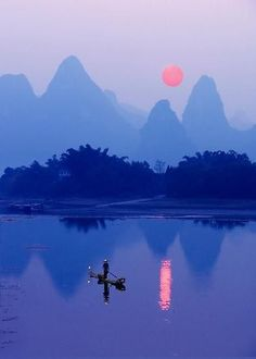 A Cormorant Fisherman at sunset on the Li River near Xingping - Guangxi Province, China.