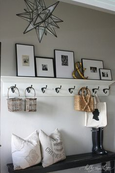 Love the black bench, hooks, and frames of family members as you walk in.