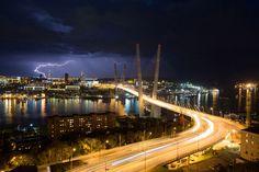 Lightning strikes the city skyline at night beyond the Golden bridge on Golden Horn Bay in Vladivostok, Russia