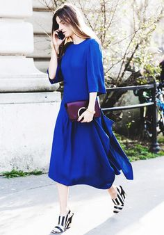 A blue midi dress is paired with striped wedges and a burgundy clutch