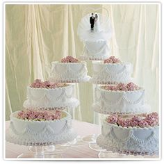 Anne:  Beautiful icing roses adorn these seven majestic tiers accented with fine Cornelli Lace and scallop draping.    The individual Crystal Splendor stands allow imaginative display opportunities sure to fit beautifully the design of your wedding table.  #bakery #cake #wedding