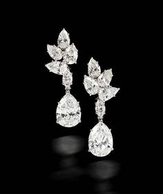 A pair of diamond pendant earrings, Harry Winston, 1967. each designed as a pear-shaped diamond, weighing 3.90 and 3.43 carats