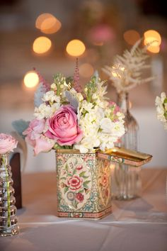 A sweet vintage centerpiece we love! {Blume Photography} Vintage tins for vases... be sure to use a jar inside or they will leak.