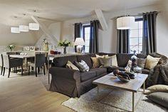 Obývací pokoj volně navazuje na jídelnu. Celému prostoru dominují zemité tóny, v čele s hnědým a hnědošedým odstínem. Pohovka byla pořízena v IKEA, ostatní nábytek je atypické výroby podle návrhů designéra a majitele. Osvětlení pochází z dílny české firmy Rendl.