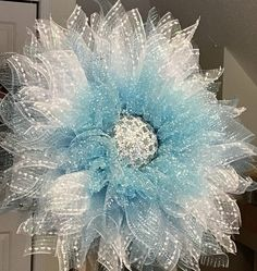 Beautiful Christmas Flower Wreath. Looks like a snowflake. Will add sparkle to your Christmas party. Blue and white deco mesh wreath. Looks like it is covered with snowflakes! The center sparkles with snowflakes buttons. Lomey Gems add even more magic! The light reflects off of the center. Perfect forgetting guest at the front door. Add Christmas cheer to you indoor decor. Materials: white snowball deco mesh light blue metallic deco mesh light blue with snow-spattered deco mesh 12 inch wi...