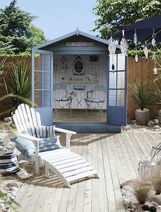 Cute beach style garden design idea, complete with shed (beach hut), hanging fish & more.