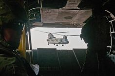 U.S. Army Spc. Devon Boxa (standing) from San Angelo, Texas, a member of Company B, 7th Battalion, 158th Aviation Regiment, watches another CH-47D Chinook out the back door of her Chinook as the two choppers take off from Kabul on their way to Jalalabad Dec. 17