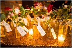 Small glass vases holding a single flower at a sparkly escort card table covered in sequins and candles. Hang tags with guests' names attached to each bottle.