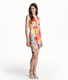 Fitted, knee-length sleeveless dress in textured woven fabric with a seam at waist. Visible zip and slit at back. Lined.