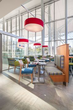 Cafe Ami at UBC in Vancouver by SSDG Interiors Inc. - wood curved banquette seating, striped upholstery, large red pendant lights, natural light, bright, colorful, cafe