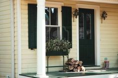 Front house / home entrance with rubber boots, stack of wood, planter, lantern and black shutters and door Stock Photo