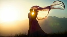 Foto de los novios a contraluz con el velo de la novia ondeando al aire y dibujando un corazón entre sus cuerpos.