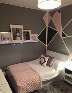 Grey and pink teen girls bedroom. Geometric walls with picture shelf