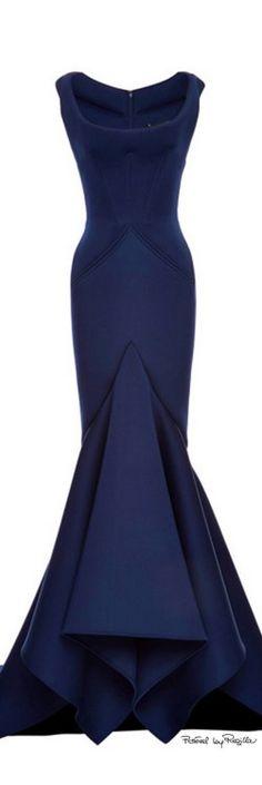 Este vestido es ceñido hasta la rodilla, en la que se abre y forma un poco de vuelo. La tela es de un color azul marino. Tiene un cuello de campana (abierto) de tirantes finos. En la cintura empieza un pico, y mas abajo, otro a la altura de la entre pierna. Es largo hasta cubrir el pie. Es un vestido muy elegante.
