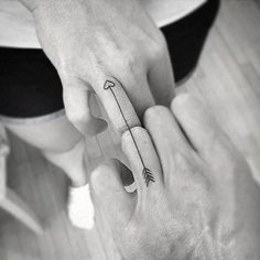 Matching arrow tattoo on the ring fingers.