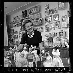 Ruth Handler, executive of Mattel Toy company, posing with collection of Barbie dolls,