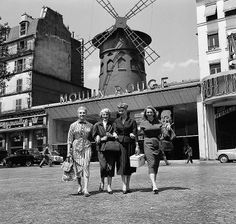 old photo of women in front of moulin rouge in paris