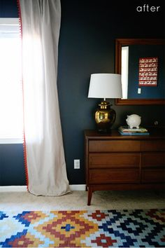 navy walls, gold lamp, cool ethnic looking rug over wall-to-wall carpet (rug from overstock.com), vintage dresser