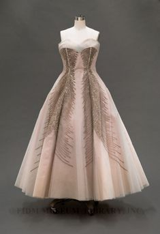 """Evening dress, 1953. """"This Gothe gown features a rounded sweetheart neckline and glittering sequin embellishment. It has bodice boning and princess seams, which are reinforced at the waist with curved metal rods. This inner structure helps gown maintain its elegant silhouette. The soft pink color, in this case with a white net over-layer, is typical of the era."""""""