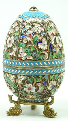 Fine Decorative Arts Finely Crafted Russian Silver Egg with Multicolor Cloisonne Enameled Design Throughout. Has Cabochon Ruby to Top and Bottom. Includes Silver Figural Fish Footed Stand. Measures 3 7/8 Inches in Height + 5/8 Inch Base height