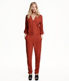 Check this out! V-neck jumpsuit in woven fabric. Concealed button placket, long sleeves with tab and metal buckle, and chest and side pockets. Elasticized seam at waist, textile belt with metal buckle, and long, tapered legs. $49.99