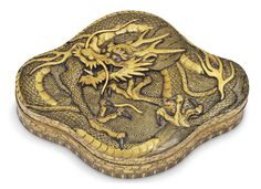 Christie's Japanese Craftsmanship: Art of the Meiji Period. A Fine Komai Metalwork Box with a Dragon, Signed Kyoto ju Komai gen sei, Meiji period (late 19th century). Of lobed form, the box and cover finely inlaid in gold and silver nunomezogan and takazogan [high-relief inlay] with a dragon against a geometric ground, the sides similarly inlaid with grapevines above a band of stylised lappet to the bottom edge, the base with signature.