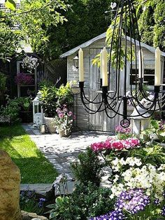 in the garden~lots of charming details. Love the shabby white shed and chandelier. Recreate the paint look by brushing white paint and rubbing off the excess with a cloth.