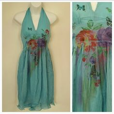 """Flowers and Butterflies"" Dress Brand new with tags!  Flowers and butterflies sky blue halter top dress. Small pleats are all over the runways and this dress is covered in them at the bottom.   Material is 100% polyester  Dress is sheer on top and has blue lining Length approx 30"", but will vary depending on where to tie the neck. a'gaci Dresses Midi"