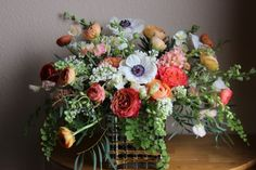 Garden style wedding centerpiece includes Garden roses, lilac, anemone, poppies, ranunculus, sweet peas, maindenhair fern, larkspur, eucalyptus and hyacinth photo by Sophisticated Floral peach coral