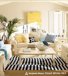 Beach cottage livingroom... Love the Black and white rug with the spashes of yellow and blue!