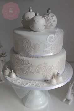 Two deep layers of vanilla sponge and carrot cake for this glittery white wedding cake. It was topped with three vanilla sponge cake baubles. X