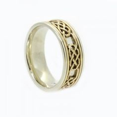 Two tone gold celtic mens wedding ring, 7.0mm wide band x 2.0mm deep with white gold base with yellow gold inlay with saw pierced celtic design and white gold side rails.