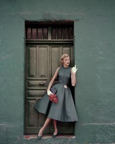 Model standing in a doorway wearing a dress by Heatherlane ✨ Glamour, 1955 📷 by Leombruno-Bodi