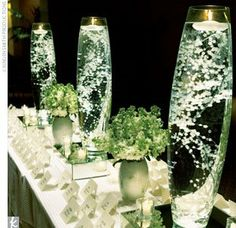DIY Centerpiece: cylinder vase,   floralytes(?), baby's breath, floating candle, sitting on a mirror.