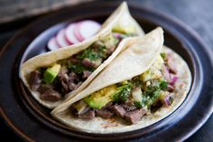 Classic Mexican tacos de lengua, beef tongue which has been braised with garlic and onions, finely chopped, and served with salsa verde and avocados.