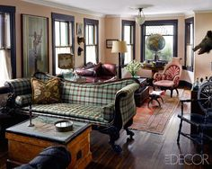 In the parlor of designer Ken Fulk's Victorian cottage in Provincetown, Massachusetts, a 19th-century scroll-arm sofa is upholstered in a Ralph Lauren Home plaid, the antique sea captain's chest was purchased at the Brimfield Antique Show, the pink armchair is from the 19th century, and the 18th-century leather sofa is English. An antique Khotan rug tops the original maple floor, and the walls are painted in Farrow & Ball's Setting Plaster.