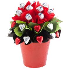 A Rose Bloom - A rose would smell almost as sweet as this decadent chocolate bouquet! Ten Baci chocolates sit atop a garden bed of red and silver Belgian chocolate hearts, ripe for the picking. This elegant bloom is perfect as a unique gift or tasteful table centre.