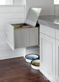 kitchen boasts a small nook filled with pert food bowls tucked under a pullout pet food storage drawer topped with thick concrete countertops