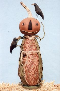 "Corny Pumpkin Man is the perfect fall gentleman as he welcomes some visiting black crows. He is 24"" tall (including his stem and the crow on top of his head). His big pumpkin head is made from muslin that has been painted and sanded and he has a real dried pumpkin stem to finish him. His ""corny"" body is made from fabric with a corn kernel or Indian corn print. He is weighted and attached to a wood base."