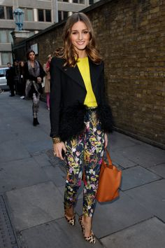 Olivia plays to fashion whimsy in Topshop floral pants, a citrus-hued tee and a pair of leopard print Mulberry heels while attending the Uni...