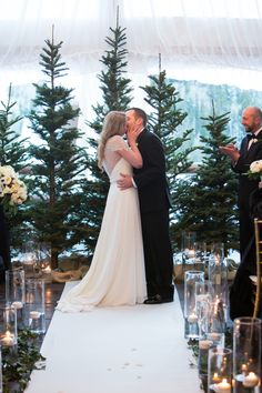 Bride and groom kiss during tented wedding ceremony with evergreen trees, chandelier, and candles | Winter wedding at Stein Eriksen Lodge in Deer Valley, Utah. Black tie wedding, under a soft fabric tent, with glowing candles, gold Chivari chairs, lush white flowers, evergreens trees and branches, and black accents | Planning: Soiree Productions | Flowers: Decoration Inc. | Photography: Melissa Kelsey Photography | http://www.melissakelseyphotography.com