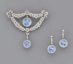 A BELLE EPOQUE SAPPHIRE & DIAMOND BROOCH & A PAIR OF EAR PENDANTS   The central circular-cut sapphire & diamond cluster drop within the rose-cut diamond floral wreath with diamond bow terminals, suspending a sapphire & diamond drop, earrings en suite, adapted, mounted in platinum, ca 1905, brooch 6.7cm high, in original cream leather fitted case. ❤❤❤❤
