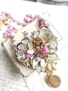 I created this delicately leafed locket necklace with the focal point being a high end vintage brooch. The brooch was a three petaled flower with pink rhinestone stamens, to which I carefully added gold leaves, Swarovski crystals and flowers. Its a bit like tiny flower arranging! The chain is