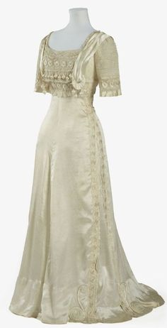"Evening Dress: ca. 1905-1909, silk satin. ""This dress epitomises the elegant feminine fashions of the well-to-do in the Edwardian period, particularly in its use of soft flowing pale silk, extensive use of lace and net, and in the ornate decoration of the bodice."""