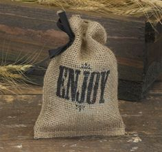 "Use these Burlap Favor Bags for your eco-friendly wedding, bridal shower or special event.  You can put a special treat in them for your guests or use them for the candy buffet at your event.  These burlap bags are simple, yet beautiful, and come complete with a twine drawstring closure, a black 3/8"" satin ribbon and an ""Enjoy"" design printed in black."