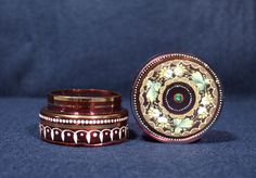 """Beautifully decorated Bohemian glass lidded pot. 19th century. Red glass with enamel and gilt decoration to the top and sides, and a green """"jewel"""" at the centre of the lid. Antiques Atlas #antiqueglass #bohemianglass #decorativeglass Antique Glass, Red Glass, Class Ring, 19th Century, Centre, Enamel, Bohemian, Jewels, Decoration"""