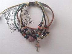 Pulsera de cuero y cordón con nudo corredizo, abalorios de colores y charm plateado cruz.