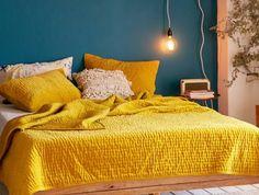 peinture murale deco bleu canard, lit en bois, linge de lit jaune moutarde, tapis beige, ampoule electrique