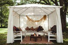 Небольшой шатер и скамейки с подушками - место отдыха для гостей жениха и невесты на свадьбе под открытым небом