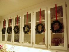 Indoor Wreaths on glass cabinets.  Plain green wreaths with red ribbon hangers.